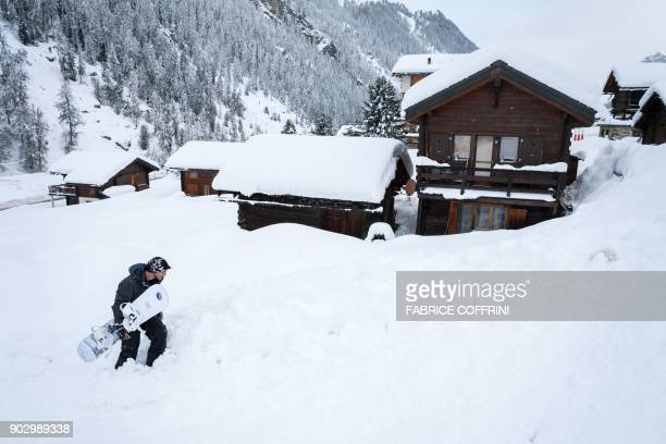A young snowboarder carries his board in the small resort of Zinal Swiss Alps on January 9 after the access road cut by heavy snowfall reopened Heavy...