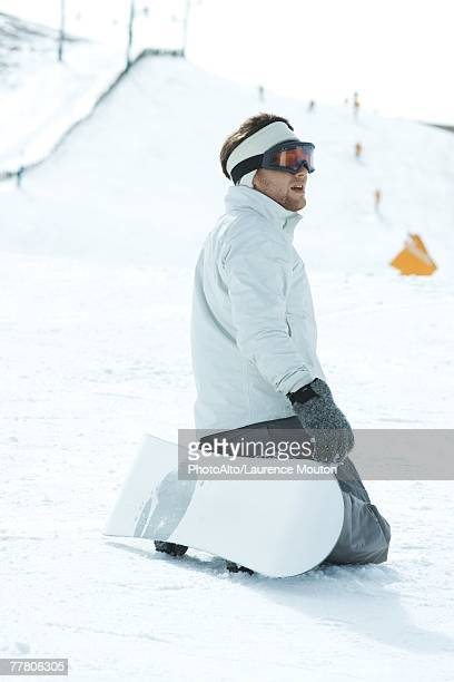 Young snowboarder kneeling on ski slope, looking away, side view