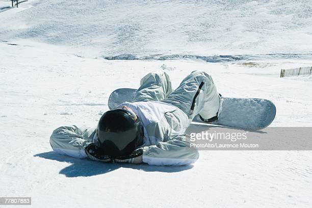 young snowboarder lying on back in snow, hands behind head, full length - legs behind head stock pictures, royalty-free photos & images