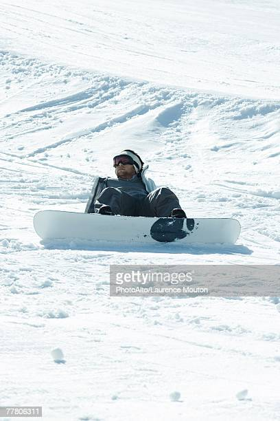 Young snowboarder sitting on the ground, fallen