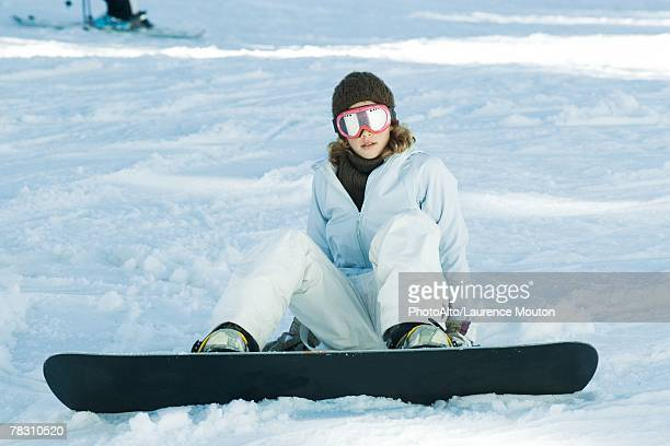 Young snowboarder sitting on the ground, looking at camera, full length