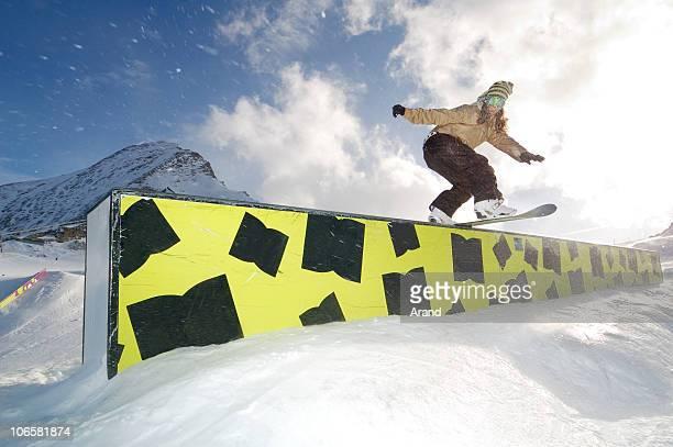 young snowboarder woman jibbing