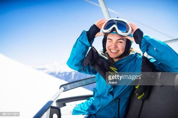 young  snowboarder woman smiling at ski lift