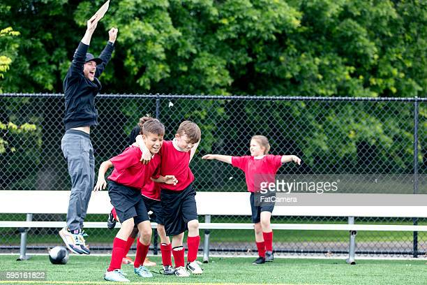 Young soccer coach celebrates with his team
