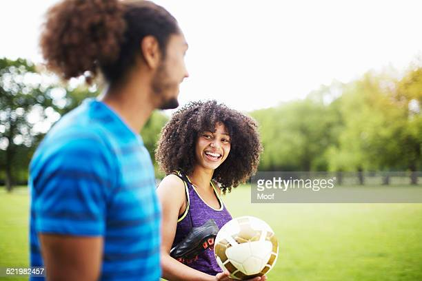 Young soccer couple chatting in park