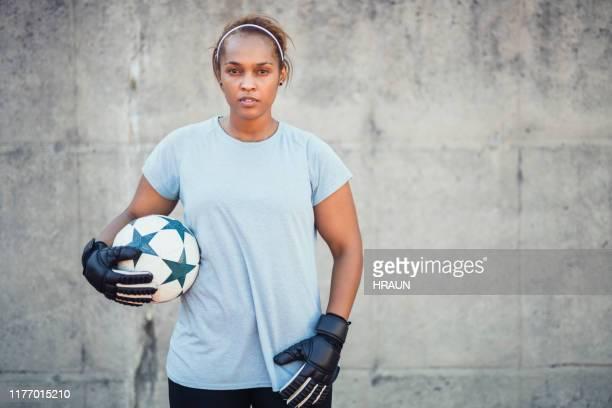 junger fußball-torwart hält ball gegen wand - torhüter stock-fotos und bilder