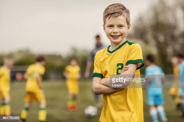 Ein junger Fußball Spieler junge posieren für individuelle Foto während einer Fußball-Trainingseinheit