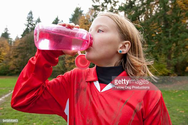 Young soccer player drinks water