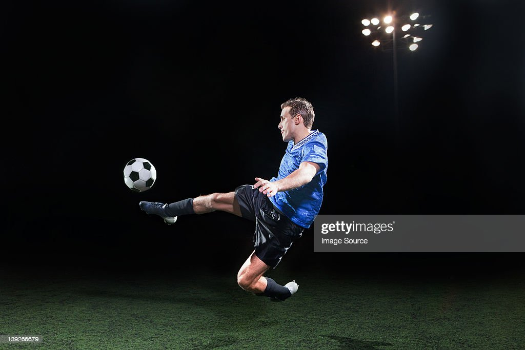 Young soccer player leaping into air to kick ball : Stock Photo