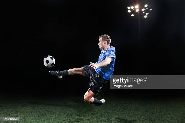 young soccer player leaping into air to kick ball - kicking stock pictures, royalty-free photos & images