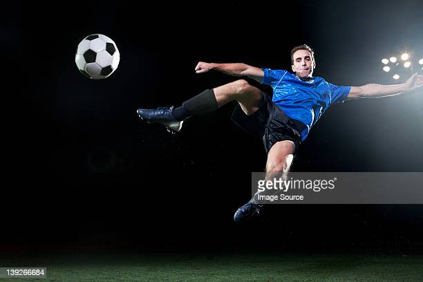 Young soccer player leaping into air to kick ball