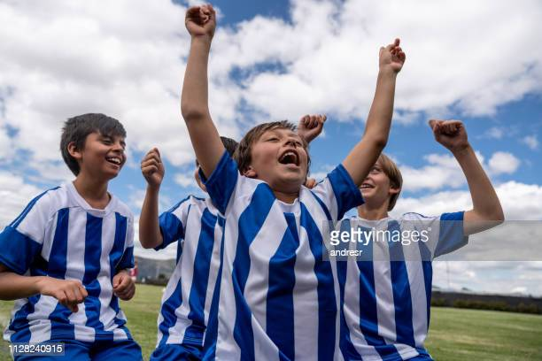 young soccer players celebrating a goal on the field - scoring a goal stock pictures, royalty-free photos & images