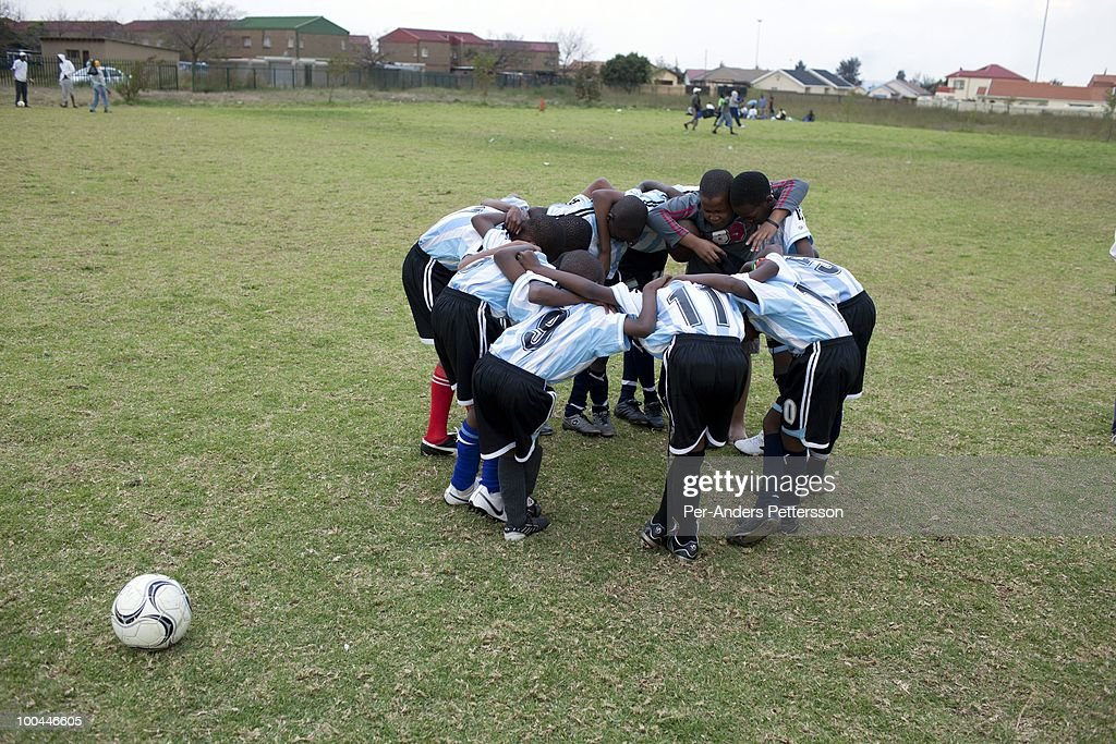 Young soccer players pray before a street soccer game on May 15, 2010, in the Jabulani section in Soweto, Johannesburg, South Africa. Thousands of young boys play soccer in townships such as Soweto, dreaming about being the next big star. The upcoming World Cup soccer tournament in the country has greatly increased the soccer interest in the country.