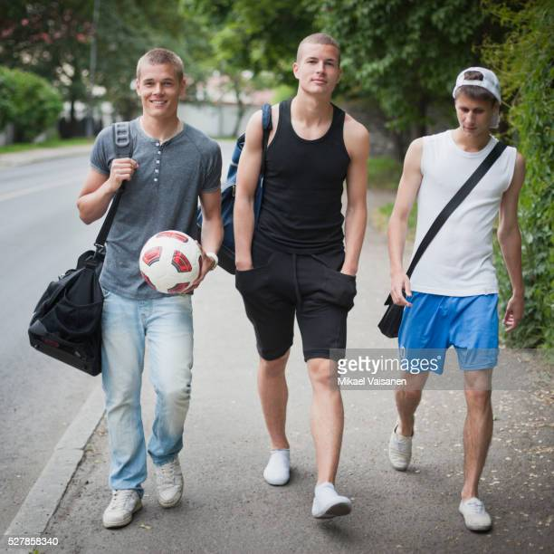 Young soccer players walking down sidewalk