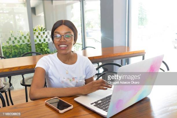 young social media expert working in the cafe. - nigeria stock pictures, royalty-free photos & images
