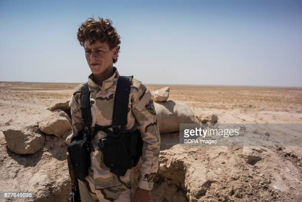 A young soldier from Quwat Al Nukhba briefly turns from his post to listen his commander on the closest frontline position to the Islamic State in...