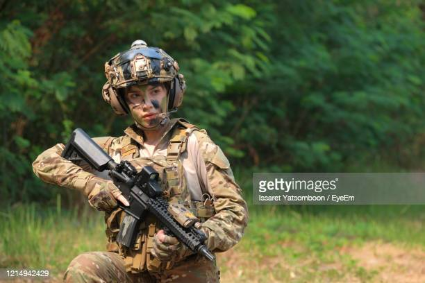 young soldier holding gun outdoors - camouflage stock pictures, royalty-free photos & images
