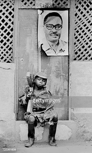 A young soldier of the Popular Movement for the Liberation of Angola is seated on a doorstep 23 February 1976 in Huambo Over his heads hangs the...