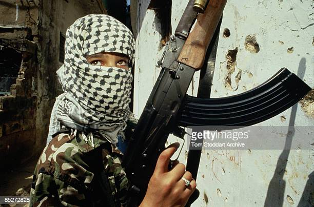 Young soldier with an assault rifle and a black and white keffiyeh in Beirut, during the Lebanese Civil War, circa 1989.