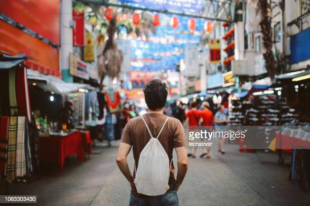 young solo traveler in kuala lumpur chinatown district - chinatown stock pictures, royalty-free photos & images