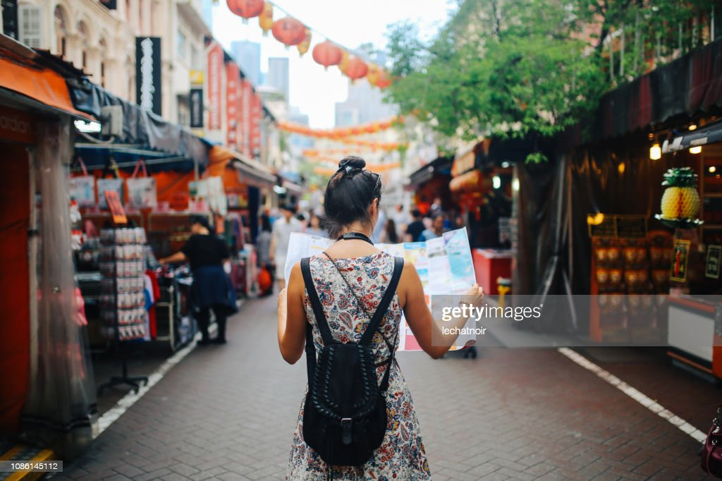 young solo traveler woman in Singapore street market checking the map : Stock Photo