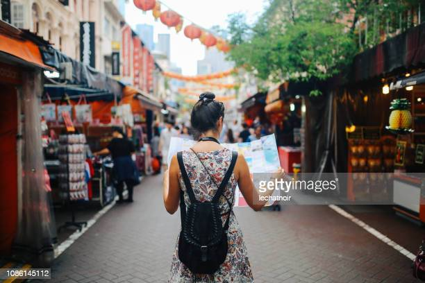 young solo traveler woman in singapore street market checking the map - vacations stock pictures, royalty-free photos & images