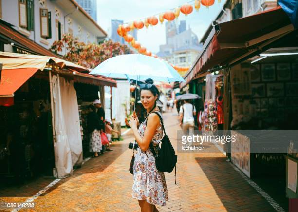 young solo traveler woman in singapore street market - multi coloured purse stock photos and pictures