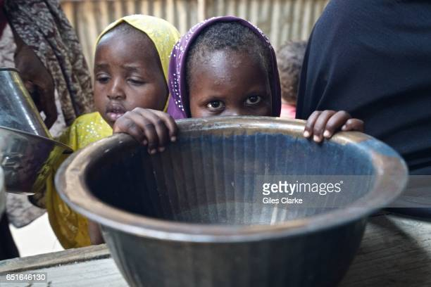 A young Somali boy peers over his family feeding bowl at a World Food program 'wet food' distribution center in central Mogadishu Hundreds of new...