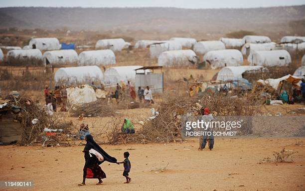 A young Somali child holds onto his mother's veil as they walk through the Kobe refugee camp near the EthiopiaSomalia border on July 19 2011...