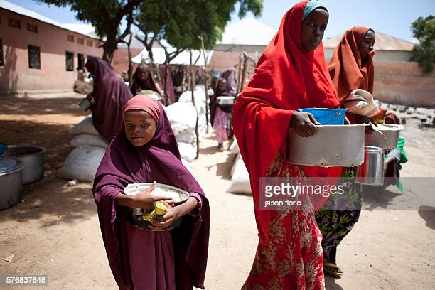A young Somali girl and mother gathers free food at a feeding kitchen operated by the Non Government Organization SAACID SAACID has been running a...