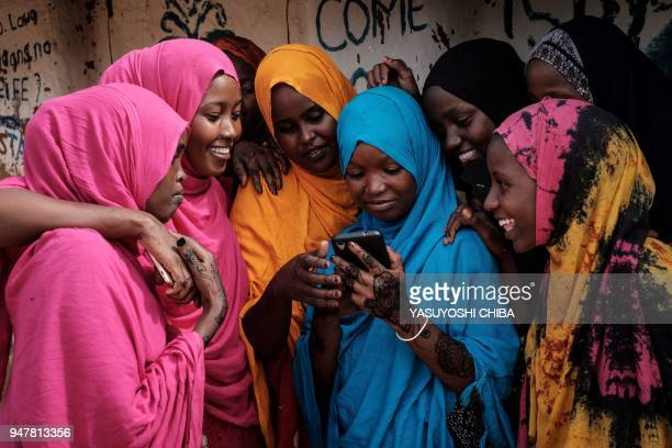 TOPSHOT Young Somali refugee women look at a smartphone as they stand together at Dadaab refugee complex in the northeast of Kenya on April 16 2018...