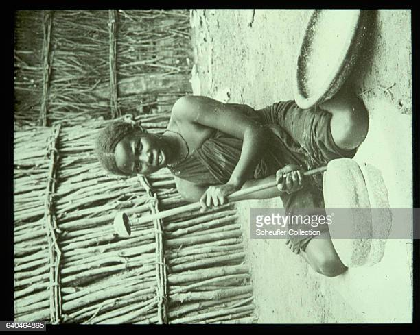 A young Somali woman handgrinds durra or Egyptian corn Somaliland 1920s