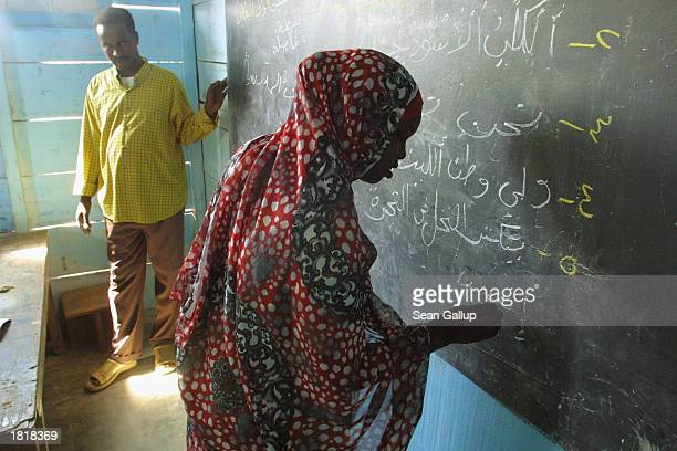 A young Somali woman writes in Arabic on a chalkboard during school at a United Nations High Commissioner for Refugees refugee camp at HolHol...
