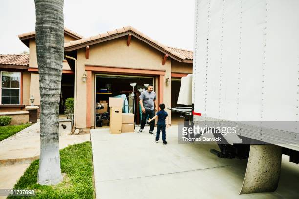 young son helping father move items from moving truck into new house - removal stock pictures, royalty-free photos & images