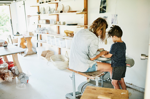 Young son helping mother make mug at potters wheel in studio in garage - gettyimageskorea