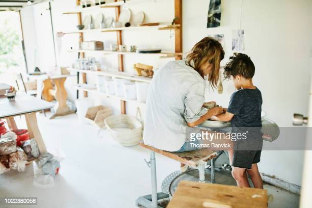 young son helping mother make mug at potters wheel in studio in garage - wirkliches leben stock-fotos und bilder