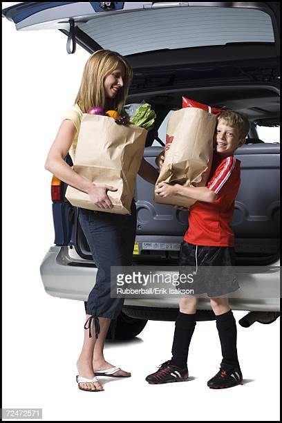 Young son helping mother with groceries