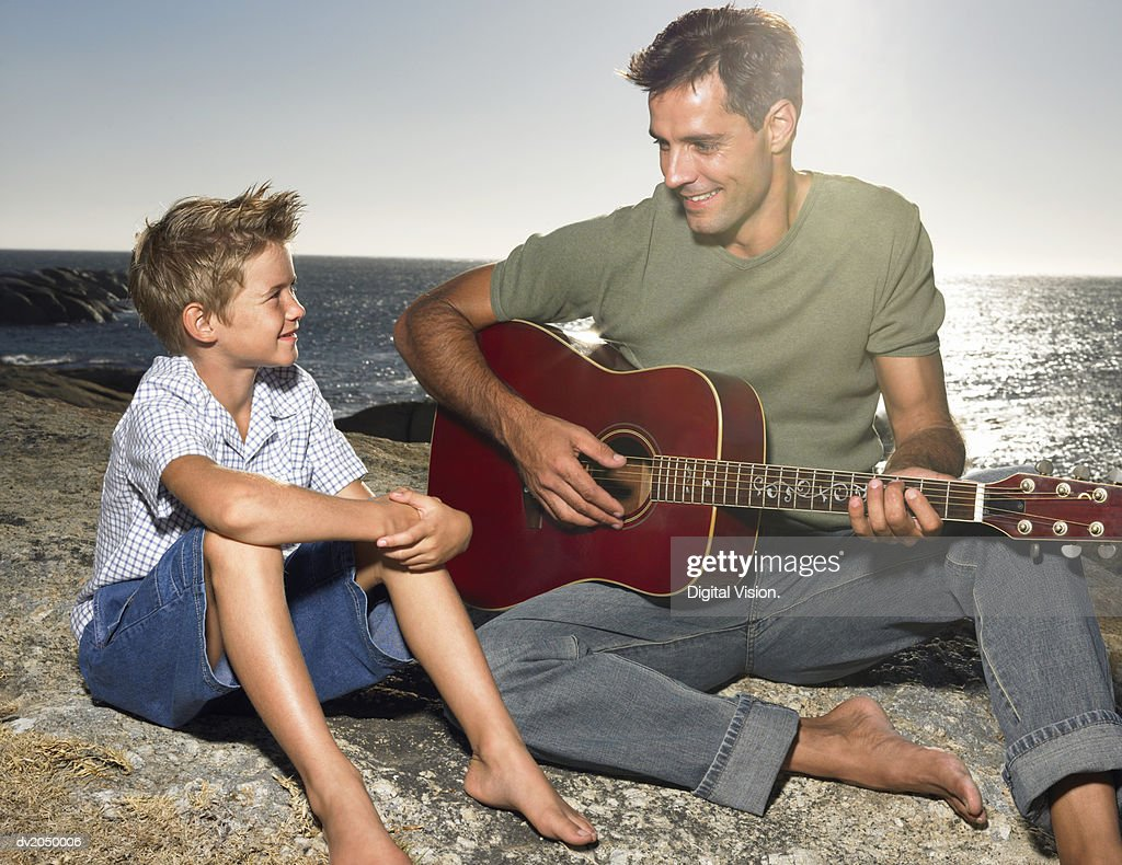 Young Son Sitting on a Rock with His Father who is Playing an Acoustic Guitar : Stock Photo
