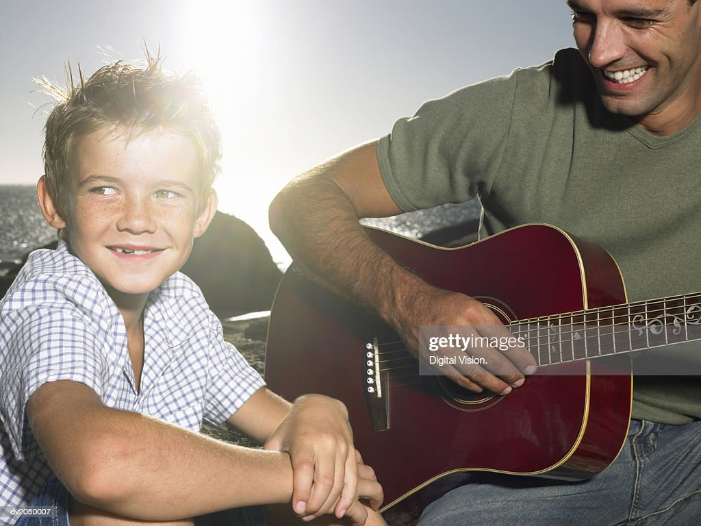 Young Son Sitting with His Father who is Playing an Acoustic Guitar : Stock Photo