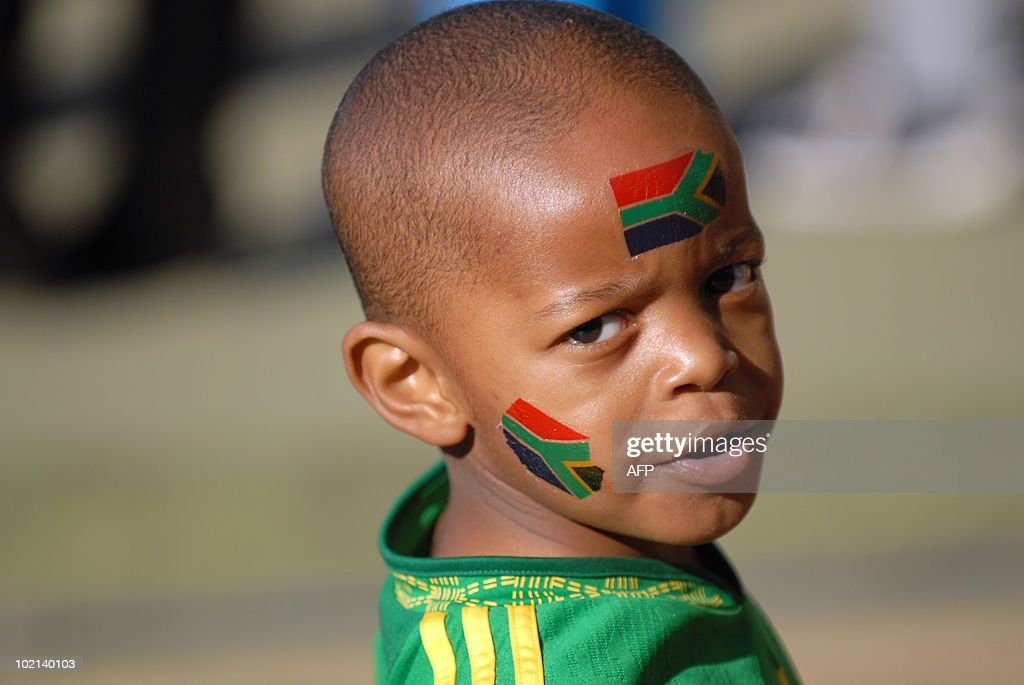 A young South African football fan with the country's colours painted on his face poses along a street in Pretoria on June 16, 2010 just hours before the 2010 World Cup football match between South Africa and Uruguay in the city. AFP PHOTO / Monirul Bhuiyan