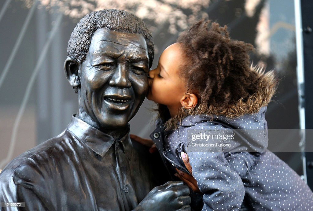 A young South African girl names Malika is lifted by her mother to kiss a statue of former South African President Nelson Mandela before a service conducted by Archbishop Desmond Tutu at the Nelson Mandela Foundation on December 9, 2013 in Johannesburg, South Africa. Mandela, also known as Madiba, passed away on the evening of December 5, 2013 at his home in Houghton at the age of 95. Mandela became South Africa's first black president in 1994 after spending 27 years in jail for his activism against apartheid in a racially-divided South Africa.