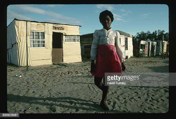A young South African girl stands outside her family's oneroom shack in Crossroads squatter camp near Cape Town