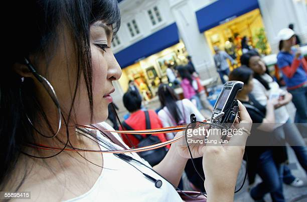 A young South Korean woman listens to her mp3 player in the street on October 11 2005 in Seoul South Korea South Korea's Ministry of Information and...