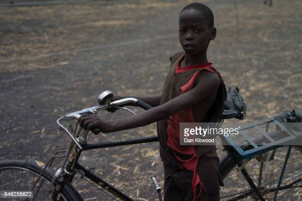 A young South Sudanese boy pushes his bike through a refugee settlement on February 25 2017 in Palorinya Uganda After registering their details...