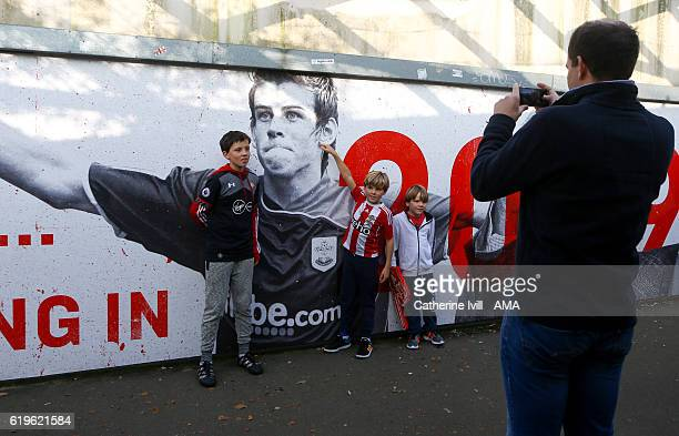 Young Southampton fans have their photo taken next to an image of Gareth Bale when he played for Southampton before the Premier League match between...