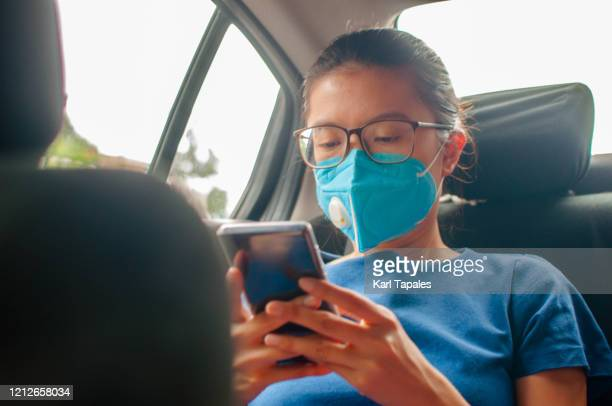 a young southeast asian female is wearing a disposable mask while using her mobile phone in the car - daily life in philippines stock pictures, royalty-free photos & images