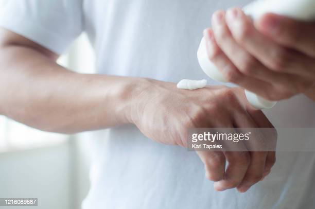 a young southeast asian man is applying lotion to his hands - solo un uomo foto e immagini stock