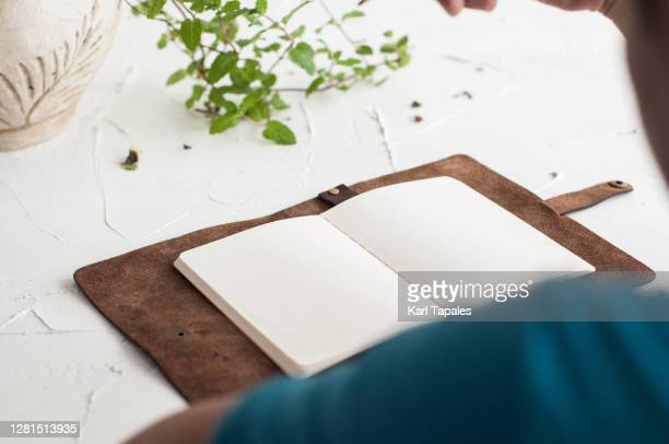 a young southeast asian man is writing on a blank note pad on a rustic table with houseplant - 肩越し ストックフォトと画像