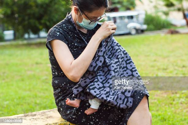 a young southeast asian mother is breastfeeding her newborn baby with nursing cover in a public park - filipino ethnicity and female not male fotografías e imágenes de stock