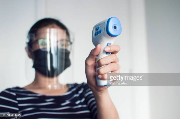 a young southeast asian woman in casual clothing with protective face mask and face shield, holding an infrared thermometer in the temperature check-point in the office - filipino ethnicity and female not male fotografías e imágenes de stock